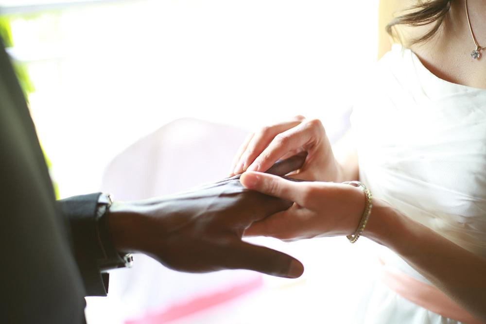 Bride Placing Wedding Band on Groom's Finger