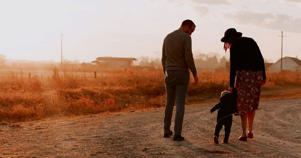 Man And Woman Walking With There Kid on a Dirt Road