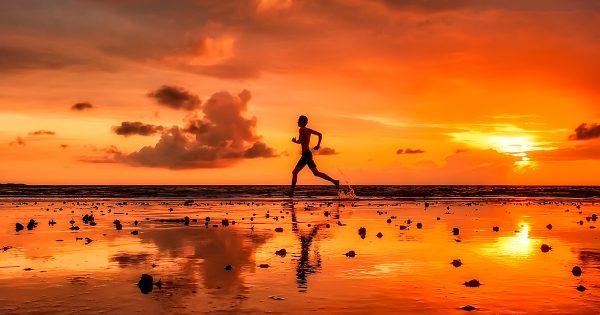 Man Exercising on Beach at Sinset
